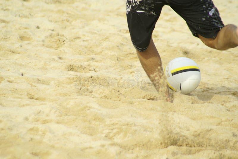 Gioco del calcio di respinta della spiaggia dell'uomo fotografia stock libera da diritti