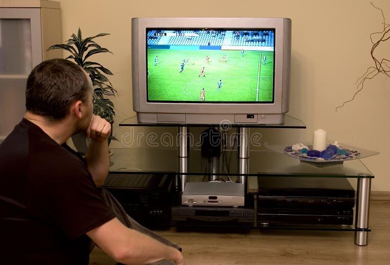 gioco del calcio di sorveglianza dell'uomo sulla TV immagine stock