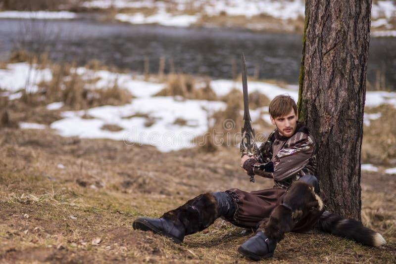 Gioco del costume Cavaliere caucasico con la spada che si siede vicino all'albero contro il fondo del fiume della natura immagine stock