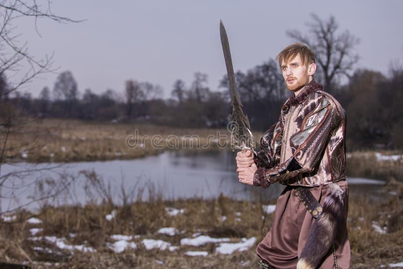 Gioco del costume Spada del wirh del guerriero che posa nel combattimento davanti all'aria aperta del fiume fotografie stock