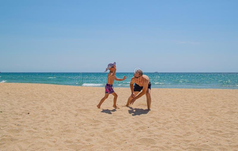Gioco del figlio e del padre sulla spiaggia immagini stock