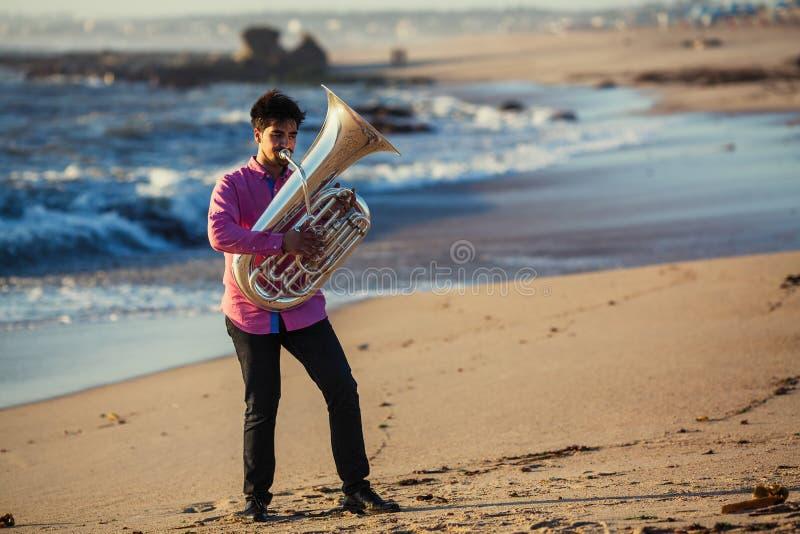 Gioco del musicista alla tuba sulla riva dell'oceano hobby immagini stock libere da diritti