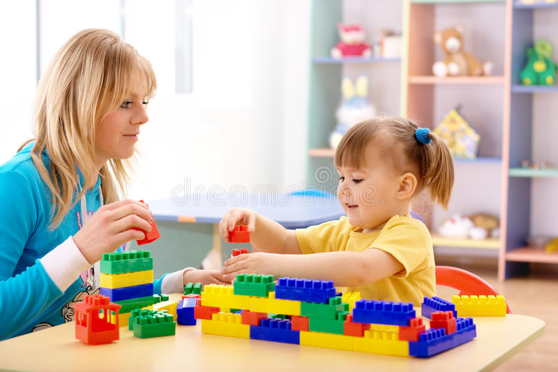 Gioco del preschooler e dell'insegnante con i mattoni della costruzione fotografia stock