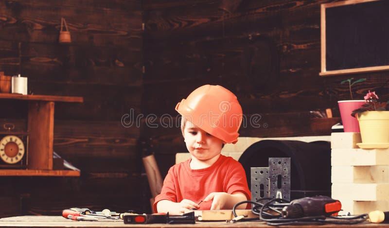 Gioco del ragazzo come il costruttore o riparatore, lavoro con gli strumenti Concetto di infanzia Bambino che sogna della carrier fotografia stock libera da diritti
