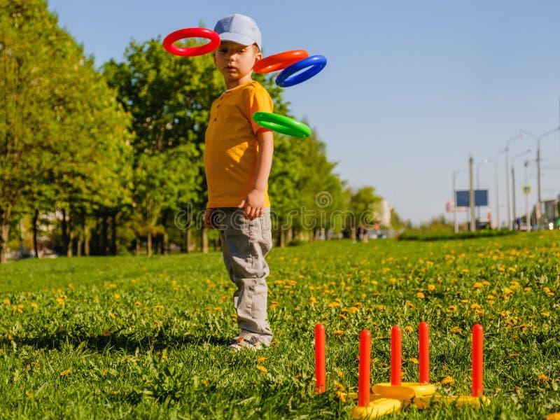 Gioco del ragazzo del piccolo bambino Suoni il gioco dell'estate del tiro su un prato inglese verde al sole fotografia stock