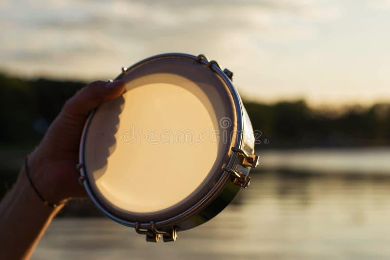 Gioco del tamburino dello strumento musicale sul cielo del fondo al tramonto fotografia stock libera da diritti
