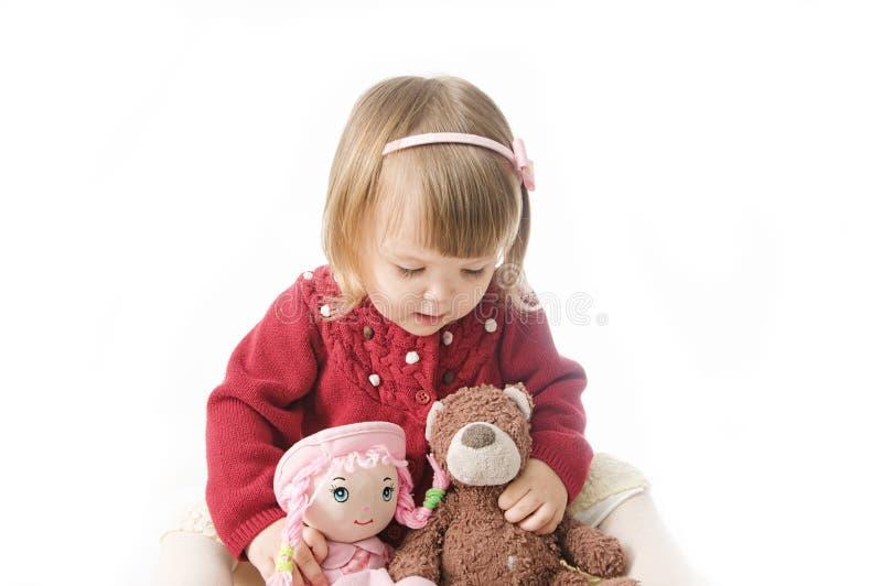Gioco della bambina bambino caucasico sveglio con l'orso e bambola su fondo bianco immagini stock