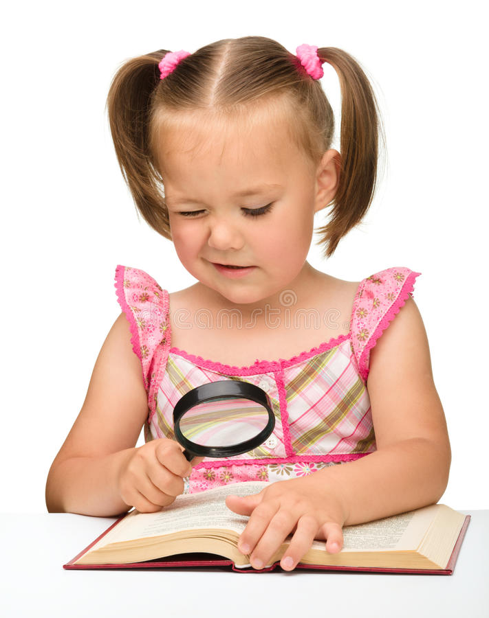 Gioco della bambina con il libro ed il magnifier fotografia stock