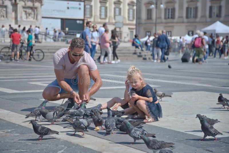 Gioco della figlia e del padre con gli uccelli in Piazza Duomo a Milano fotografia stock libera da diritti