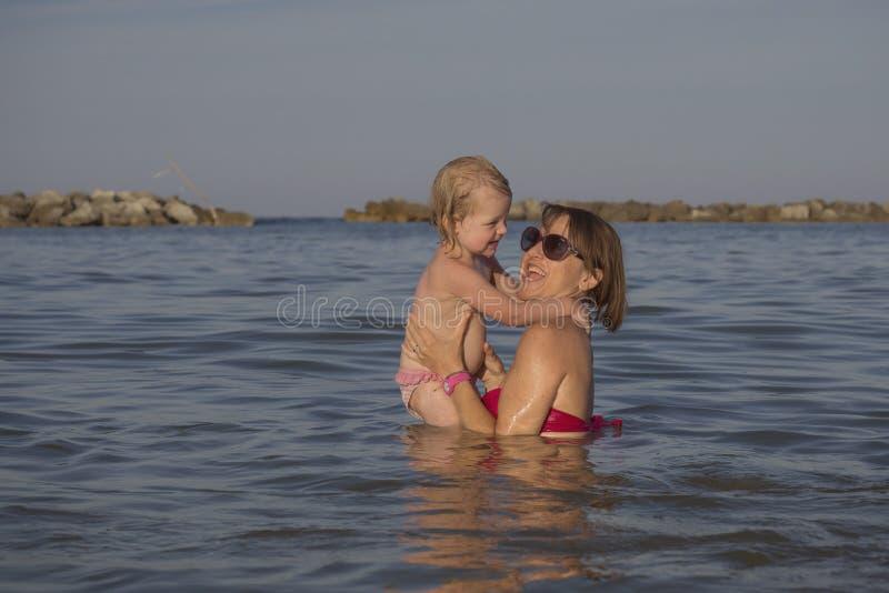 Gioco della figlia e della mamma felice in mare fotografie stock libere da diritti