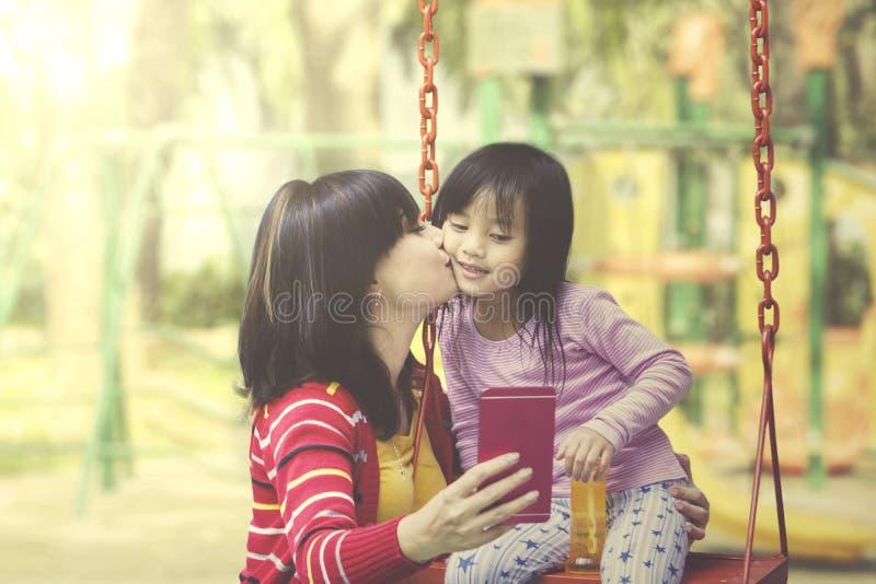 Gioco della figlia e della madre insieme al campo da giuoco fotografia stock