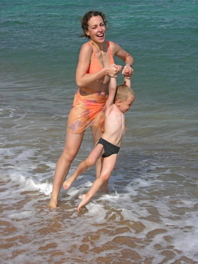 Gioco della madre con il figlio sulla spiaggia immagini stock libere da diritti
