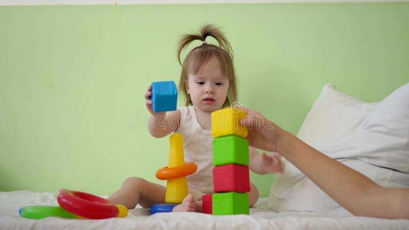 Gioco della mamma e del bambino con i cubi variopinti sul letto Giocattoli educativi per i bambini di asilo e della scuola matern fotografia stock libera da diritti