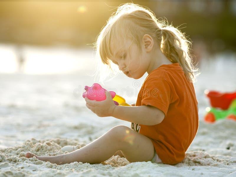 Gioco della neonata con la sabbia fotografia stock