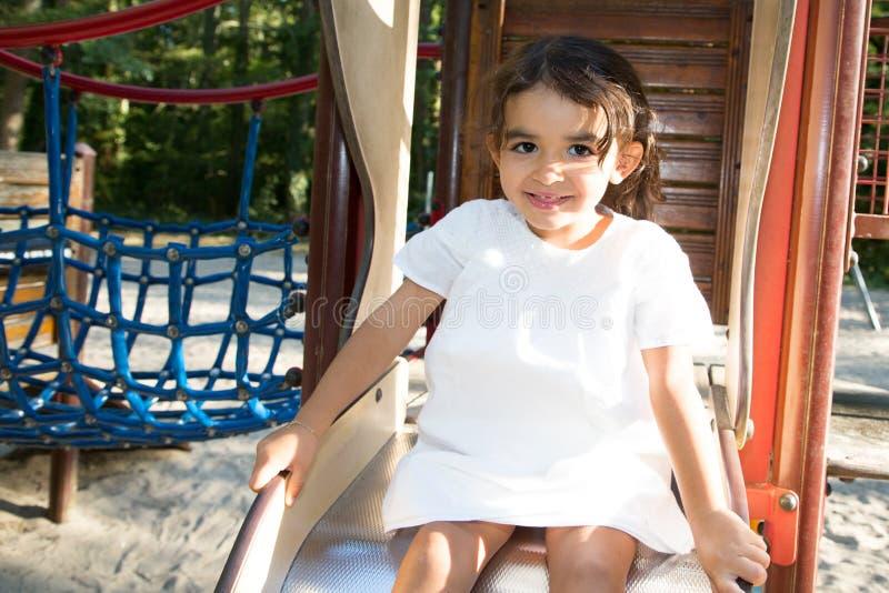 gioco della ragazza del bambino nel campo da giuoco di area dei bambini in parco fotografie stock