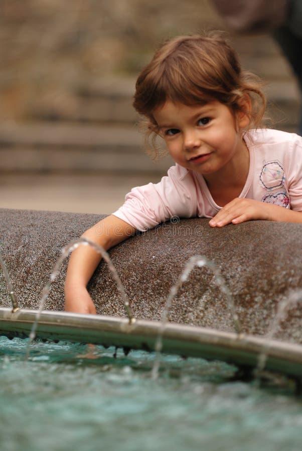 Gioco della ragazza in fontana   immagini stock