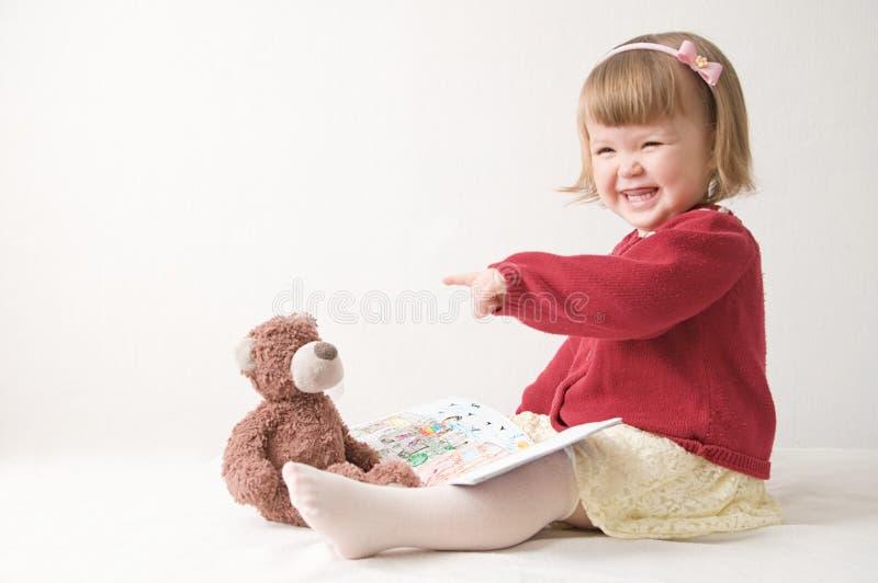 gioco della scuola con i giocattoli neonata sorridente felice elegante in vestito bambino caucasico sveglio con l'orsacchiotto fotografia stock libera da diritti