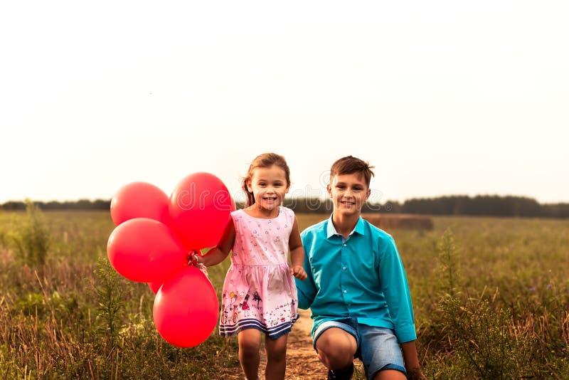"""gioco della sorella e del fratello con i palloni rossi di estate in natura """" fotografie stock libere da diritti"""