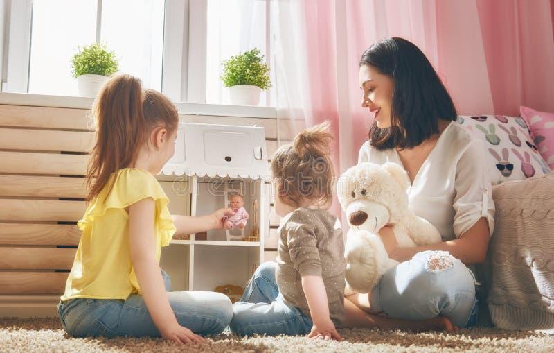 Gioco delle figlie e della madre con la casa di bambola immagini stock