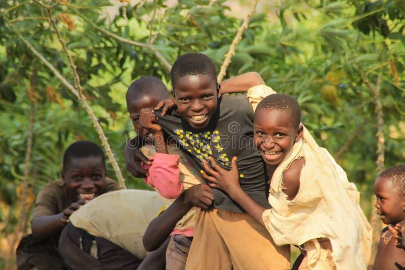 Gioco di bambini africano del villaggio vicino alle loro case nel sobborgo di Kampala fotografia stock libera da diritti
