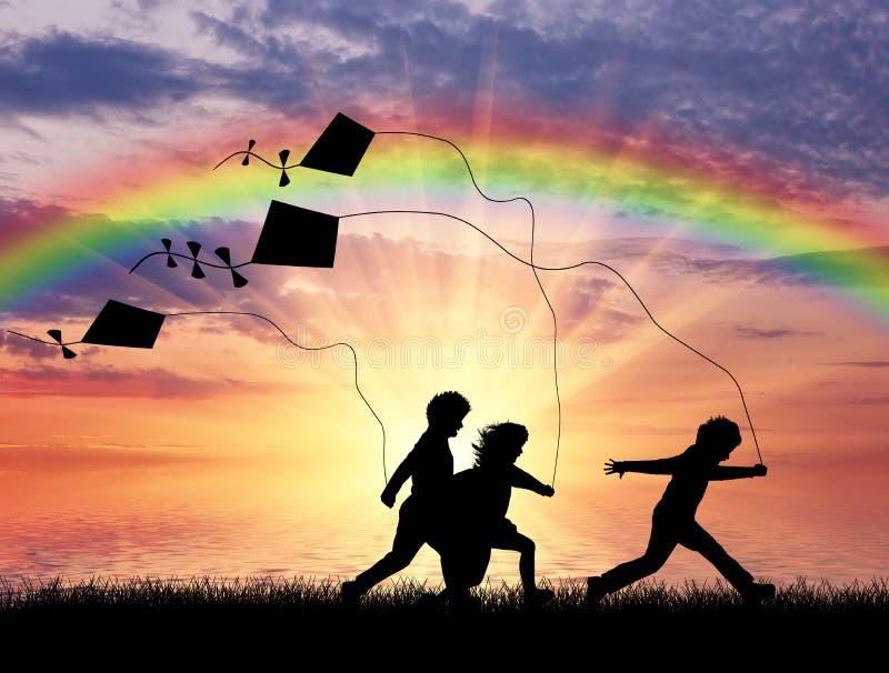 Gioco di bambini con l'aquilone al tramonto immagini stock