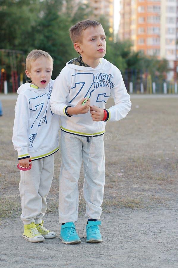 Gioco di bambini divertente e felice in un aquilone Sono vestiti in magliette felpate e pantaloni bianchi Correndo sul tramonto immagini stock