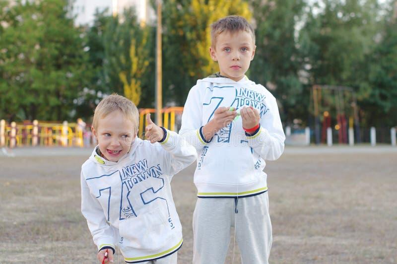 Gioco di bambini divertente e felice in un aquilone Sono vestiti in magliette felpate e pantaloni bianchi Correndo sul tramonto fotografie stock