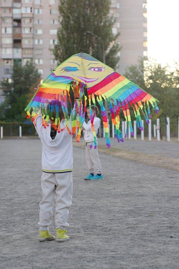 Gioco di bambini divertente e felice in un aquilone Sono vestiti in magliette felpate e pantaloni bianchi Correndo sul tramonto fotografia stock libera da diritti