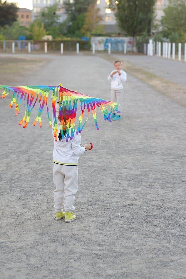 Gioco di bambini divertente e felice in un aquilone Sono vestiti in magliette felpate e pantaloni bianchi Correndo sul tramonto immagine stock libera da diritti