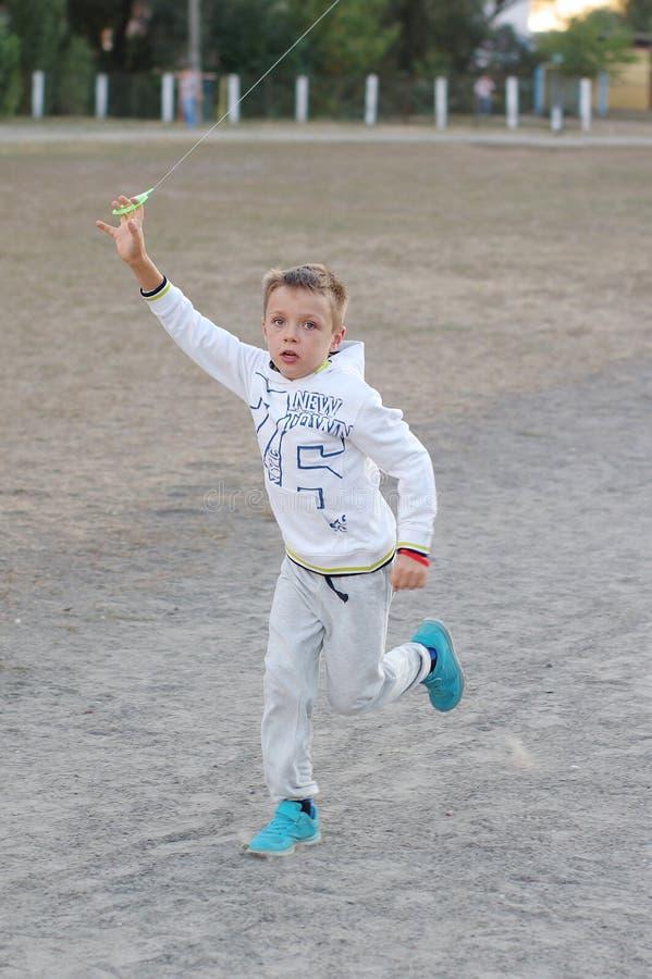 Gioco di bambini divertente e felice in un aquilone Sono vestiti in magliette felpate e pantaloni bianchi Correndo sul tramonto fotografie stock libere da diritti
