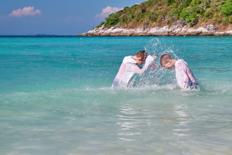 Gioco di bambini nel mare, spruzzantesi con acqua Due ragazzi in capi bianchi giocano sulla costa tropicale in acqua del turchese fotografia stock libera da diritti