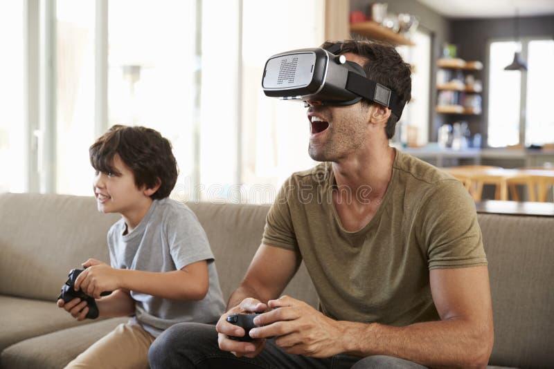 Gioco di computer di And Son Play del padre facendo uso della cuffia avricolare di realtà virtuale immagini stock libere da diritti