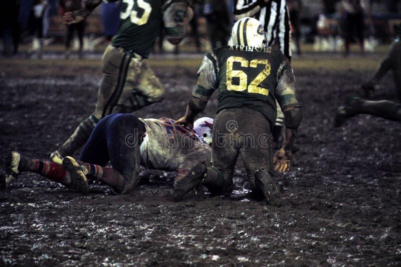 Gioco di football americano professionale nel fango fotografia stock libera da diritti