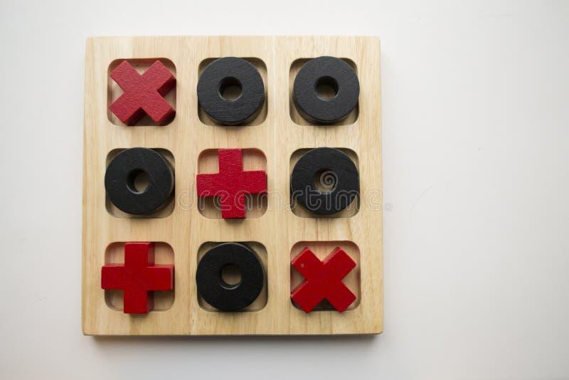 Gioco di legno del dito del piede di tac di tic su fondo bianco Croci rosse e bla fotografia stock libera da diritti