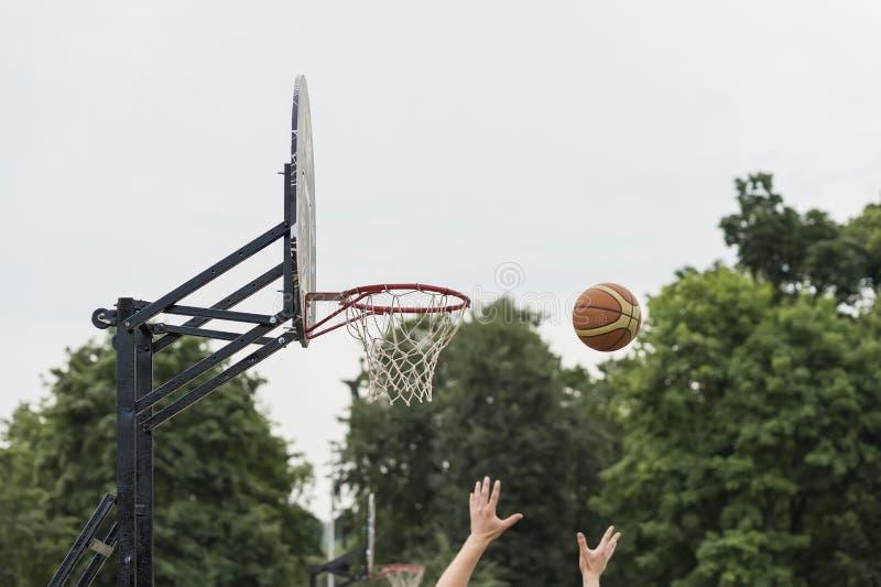 Gioco di pallacanestro della via Schermo, canestro e palla di pallacanestro su fondo del cielo, via di estate Mani di pallacanest immagini stock libere da diritti