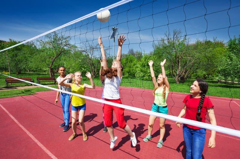 Gioco di pallavolo fra gli adolescenti che stanno giocando fotografia stock