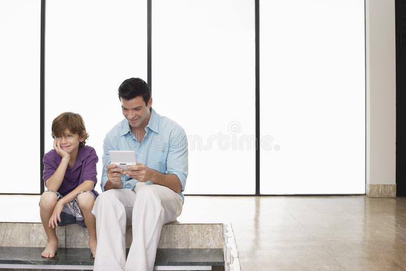 Gioco di Playing Handheld Video del padre che si siede accanto al figlio a casa immagine stock libera da diritti