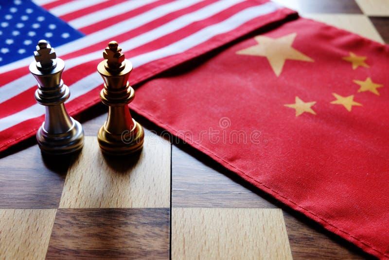 Gioco di scacchi Due re faccia a faccia sulle bandiere nazionali cinesi ed americane Guerra commerciale e conflitto fra due grand fotografie stock