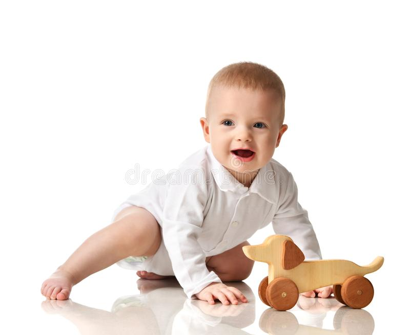 Gioco di seduta del bambino del bambino infantile del neonato con sorridere felice del giocattolo di legno del cane di eco fotografia stock