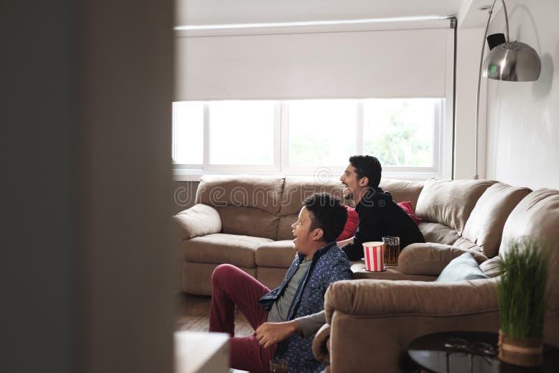 Gioco di sorveglianza di sport delle coppie gay felici sulla TV a casa immagine stock libera da diritti