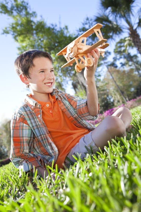 Gioco esterno del giovane ragazzo con il suo aeroplano di modello fotografia stock
