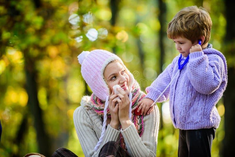 Gioco felice del figlio con la madre come medico rilassi nell'umore della primavera della foresta di autunno Freddo stagionale Gi fotografia stock