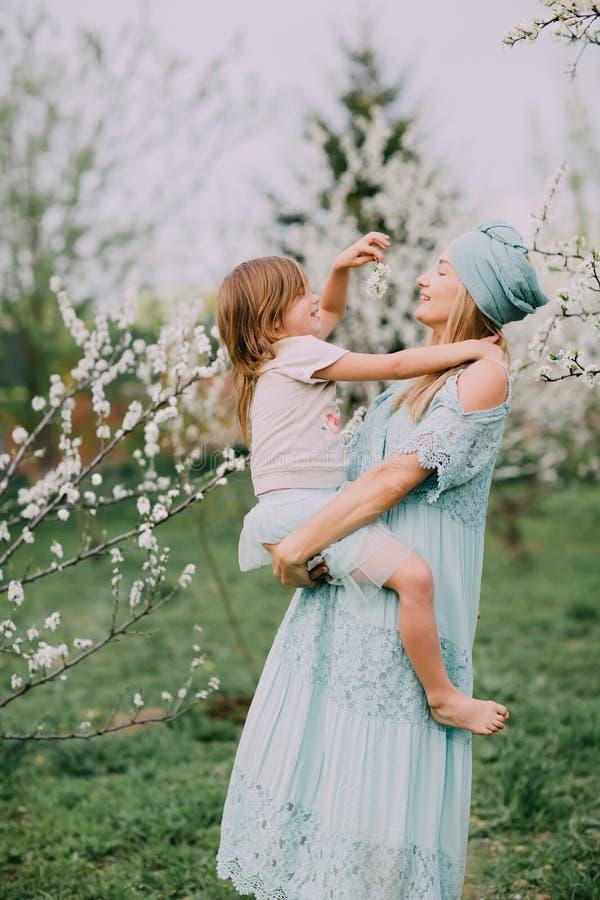 Gioco felice della mamma con la figlia su un parco della molla immagini stock