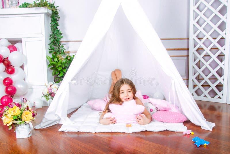 Gioco felice della ragazza a casa Bambino divertente divertendosi nella stanza di bambini immagine stock libera da diritti