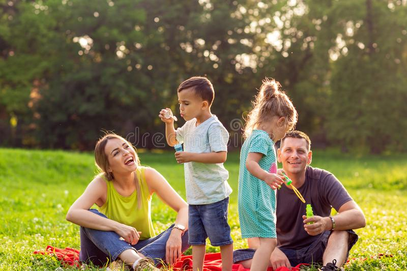 Gioco maschio e femminile felice con i bambini fuori immagini stock libere da diritti