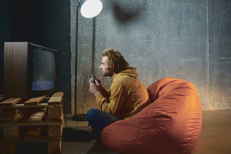 Gioco maschio interessato in video gioco fotografia stock libera da diritti