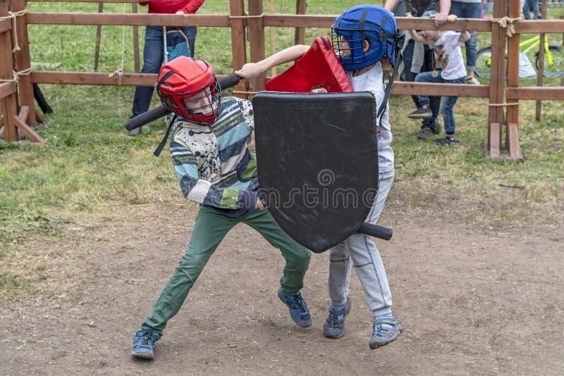 Gioco per i ragazzi I bambini combattono con le spade e gli schermi nella difesa ed in caschi immagine stock