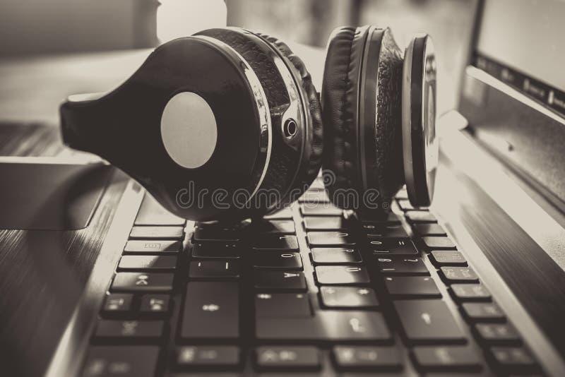 Gioco senza fili nero o Deejay Headset Lying On una tastiera del taccuino con i colori monocromatici leggermente sovraesposti immagine stock