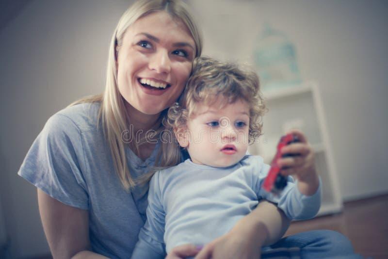 Gioco sorridente della madre con il suo neonato fotografie stock