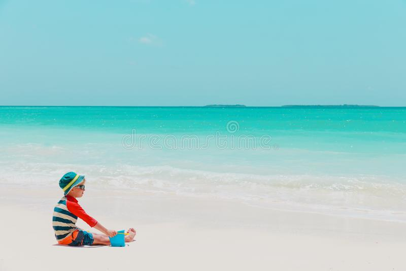 Gioco sveglio del ragazzino con acqua e la sabbia sulla spiaggia immagini stock libere da diritti